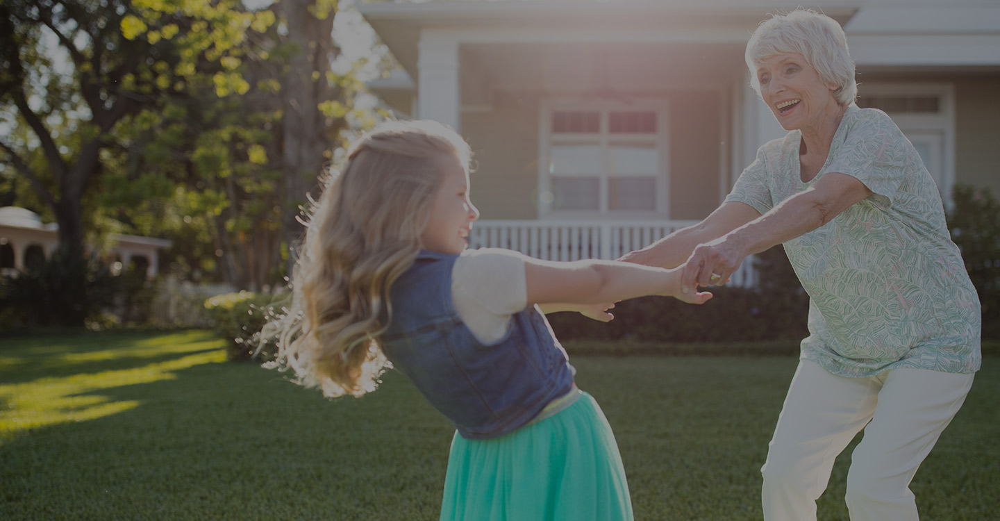 A grandmother and granddaughter dancing on their front lawn