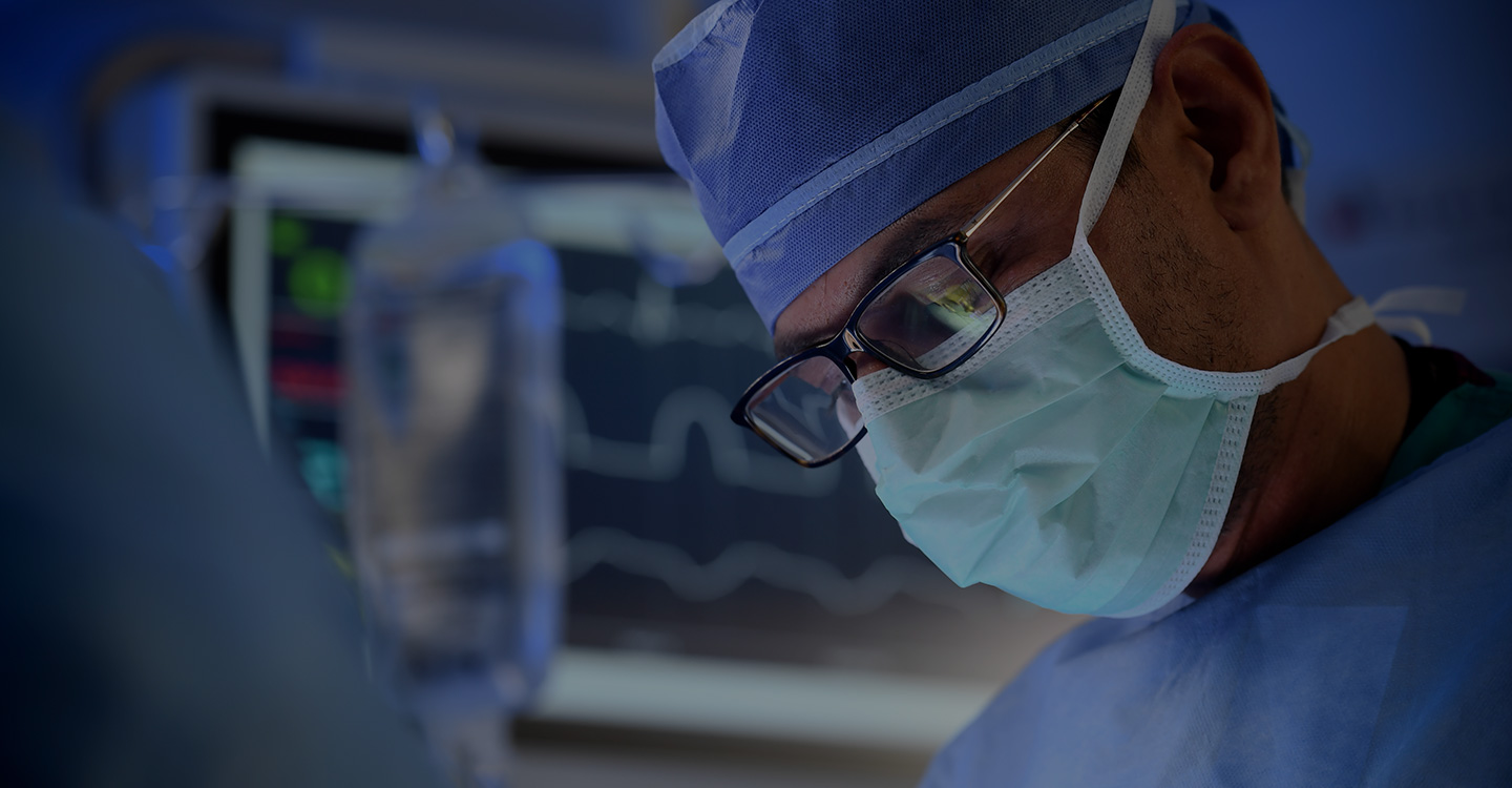 Surgeon looking down while conducting a minimally invasive procedure