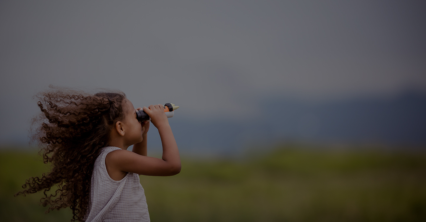 A young girl in a field looking through binoculars