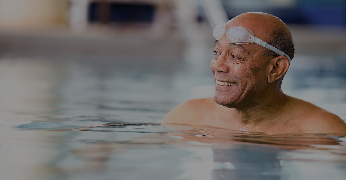 Man exercising in a pool to maintain spine health