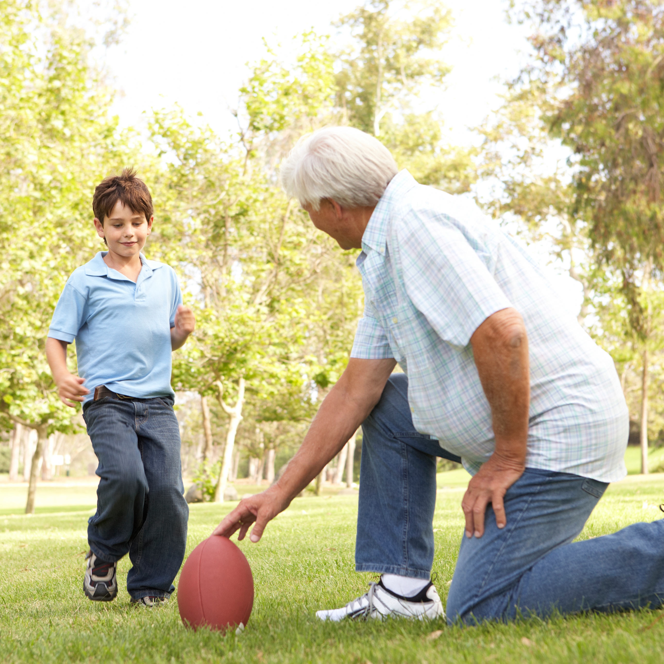 Grandfather setting up football for grandson to kick.